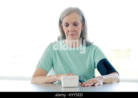 Senior woman taking her own blood pressure. - Stock Photo