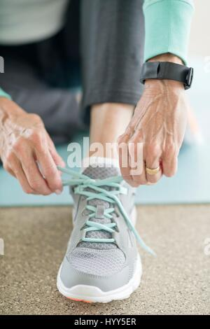 Senior woman lacing up trainers, close up. - Stock Photo