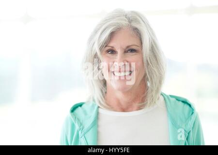 Senior woman smiling and looking at camera. - Stock Photo