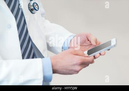 Male doctor using smartphone. - Stock Photo