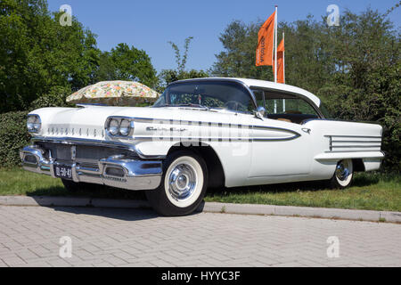 ROSMALEN, THE NETHERLANDS - MAY 8, 2016: Side view of a parked 1958 Oldsmobile Eighty Eight classic car. - Stock Photo
