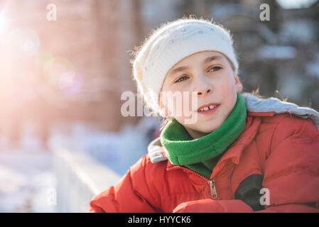 Little Girl wearing winter hat and red jacket Enjoying outdoor - Stock Photo