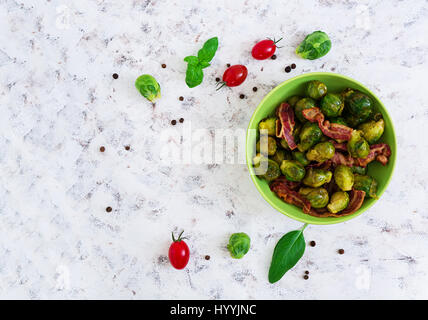 Roasted brussels sprouts with bacon on white background. Top view