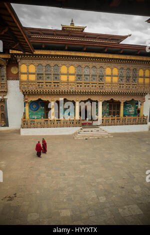 Two monks meeting in the second courtyard in Punakha Dzong (Bhutan) - Stock Photo