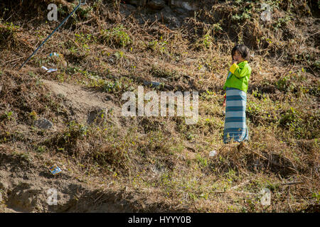 Young Bhutanese girl in a kira standing in the middle of plastic garbage - Stock Photo