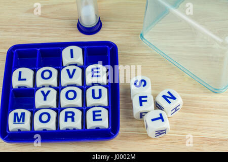 I LOVE YOU MORE Wording Game Blocks in Blue Tray on Wooden Surface with Sand Timer and Tray Cover in the Back - Stock Photo