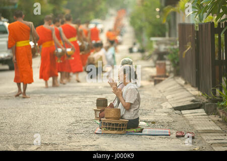 Lao People's Democratic Republic, Laos, Luang Prabang - 20 JUNE 2014: Woman prays after giving alms to buddhist - Stock Photo