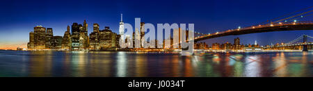 Panoramic view of Lower Manhattan Financial District skyscrapers at twilight with the Brooklyn Bridge. New York - Stock Photo