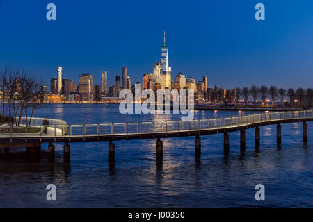 New York City Financial District skyscrapers at sunset and Hudson River from Hoboken promenade. Lower Manhattan - Stock Photo