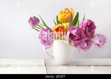 Fresh bouquet of tulips in pot on rustic wood. Vintage stile - Stock Photo