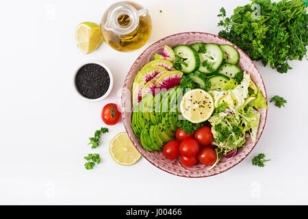 Diet menu. Healthy lifestyle. Vegan salad of fresh vegetables - tomatoes, cucumber, watermelon radish and avocado - Stock Photo