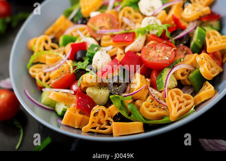 Pasta in the shape heart salad with tomatoes, cucumbers, olives, mozzarella and red onion Greek style. - Stock Photo