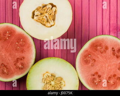 Water Melon Galia Melon and Honeydew Melon Against a Pink Background