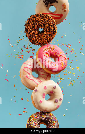 Various decorated doughnuts in motion falling on blue background. Sweet and colourful doughnuts falling or flying - Stock Photo