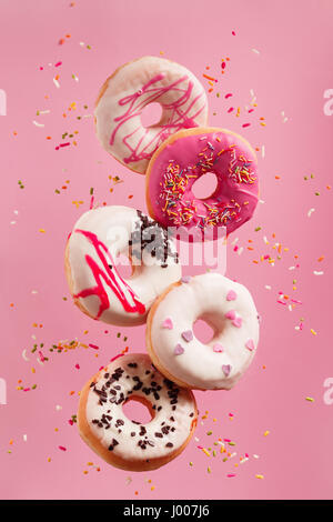 Various decorated doughnuts in motion falling on pink background. Sweet and colourful doughnuts falling or flying - Stock Photo