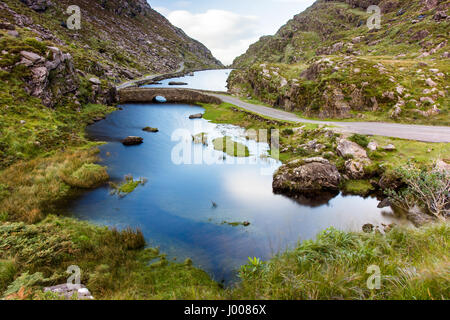 The River Loe & narrow mountain road wind through the Gap of Dunloe valley, nestled in the Macgillycuddy's Reeks - Stock Photo