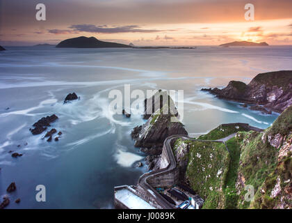 A narrow winding path leads down steep cliffs to Dunquin Pier, with the Blasket Islands beyond, on the rocky Atlantic - Stock Photo