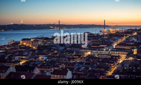The view over Lisbon's central Baixa neighbourhood and over the Tagus River to Almada, with the 25 April Bridge - Stock Photo