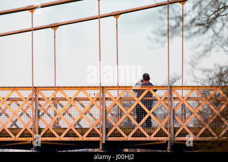 A person standing on the River Dee Suspension Bridge that crosses over the River Dee in Chester from Handbridge - Stock Photo