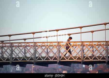 A person crossing over the River Dee Suspension Bridge that crosses over the River Dee in Chester from Handbridge - Stock Photo