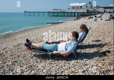 A couple relaxes on sun loungers on the pebbled beach next to Bognor pier on a warm and sunny April day at Bognor - Stock Photo