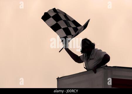 Long Beach, California, USA. 7th Apr, 2017. IMSA Official, Tani Corthell, waves the checkered flag, ending the days - Stock Photo