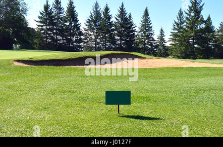 Sign in front of a golf green on a mid-summer day - Stock Photo