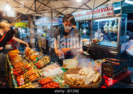 Chiang Mai, Thailand - August 27, 2016: Young man sells satay at the Saturday Night Market on August 27, 2016 in - Stock Photo