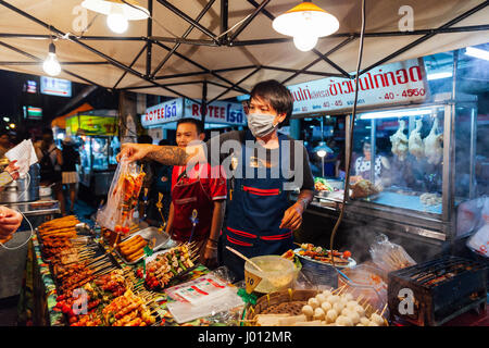 Chiang Mai, Thailand - August 27, 2016: Young men sell satay at the Saturday Night Market on August 27, 2016 in - Stock Photo