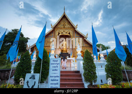 Chiang Mai, Thailand - August 21, 2016: Woman pray at the Wat Phra Singh temple decorated with Queens Blue Flags - Stock Photo