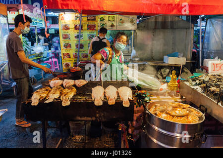 Chiang Mai, Thailand - August 27, 2016:  Thai woman cooks grilled fish at the Saturday Night Market on August 27, - Stock Photo