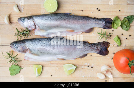 rainbow trouts on wooden cutting board - Stock Photo