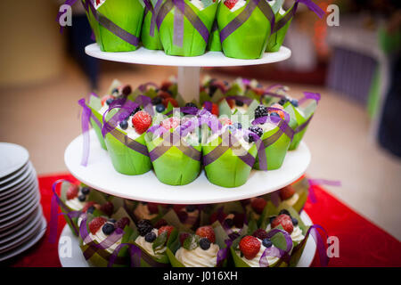 mini cupcakes on a multi level tier in different colors - Stock Photo