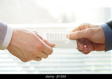 Businesspeople exchanging Visiting Card In Office with sunshine - Stock Photo