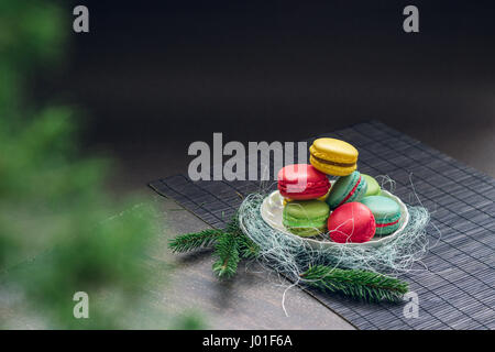 Winter still life with traditional French macaroons on the small plate and fir tree branches. Space for your text - Stock Photo