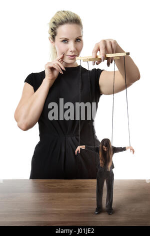 business woman puppet master pulling on strings of a doll - Stock Photo