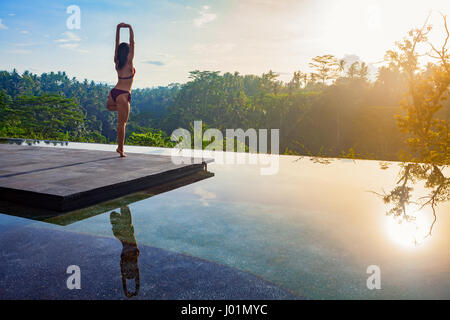 Good morning with yoga meditating on sunrise background. Active woman in bikini practicing on villa poolside to - Stock Photo