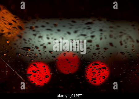 Night lights of urban traffic seen through the windshield in rainy weather. Abstract background. Concept of night - Stock Photo