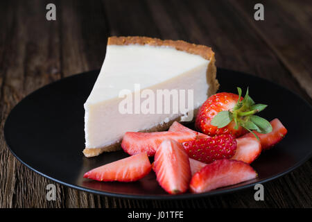 Cheesecake with fresh strawberries on black plate. Slice of plain cheesecake. Wooden table background - Stock Photo