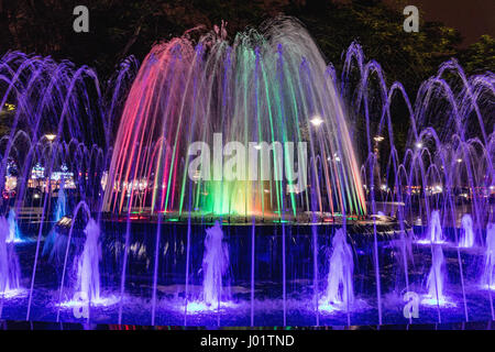 Colored fountain at might in circle inn Hai Phong, Vietnam. Brightly and colorfully lit fountain - Stock Photo
