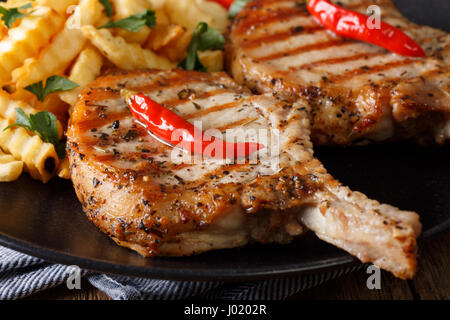 Grilled pork steak with bone, chili pepper and fries close-up on plate. horizontal - Stock Photo