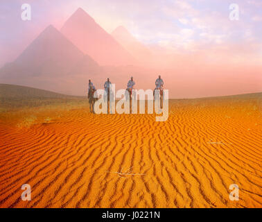 Pyramids and camelriders at dawn, Giza, Cairo, Egypt - Stock Photo