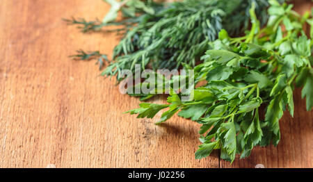 Spicy grass marjoram, dill and parsley on a wooden table - Stock Photo