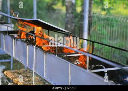 Empty Barbecue Flaming Charcoal Grill With Bright Flames Of Fire - Stock Photo