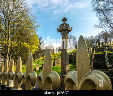 Top of an ornamental cast iron railing with gold fleur de lys making leading line foreground with gravestones and - Stock Photo