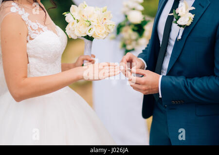 The groom dresses a ring on the finger of the bride at a wedding ceremony. Wedding in Montenegro. - Stock Photo