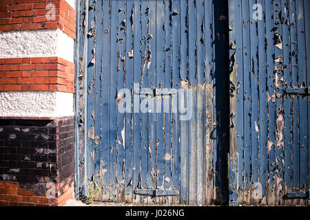 Shabby sets of garage or factory wooden doors with peeling and faded blue paint with red and white brick columns - Stock Photo