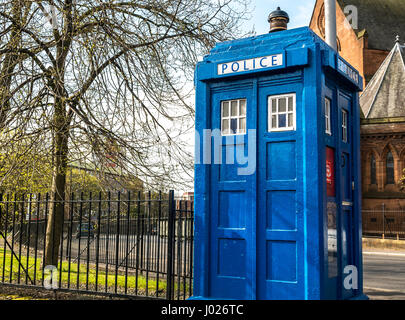 Old blue police box, Tardis, city centre street, Glasgow, Scotland, UK with red sandstone church in background, - Stock Photo