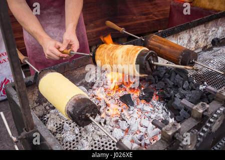 Kurtos kalacs or Chimney Cakes roll spinning over hot coals at a market stand,the typical sweet of Budapest,Hungary - Stock Photo