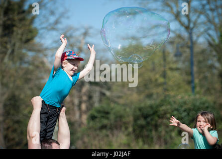 A young boy is lifted up into the air by his father so he can try and burst large bubbles floating in the air during - Stock Photo